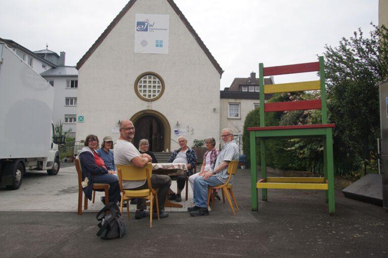 Bild einiger der Mitmachmenschen am Tisch im Hof der Werkstattkirche
